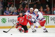 Jesper Fast #17 of the New York Rangers trips up Taylor Hall #9 of the New Jersey Devils during the first period during a preseason game at the Prudential Center on September 17, 2018 in Newark, New Jersey.