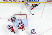 Thomas Chabot #72 of the Ottawa Senators wraps around the net and banks the puck off of the skate of Nick Holden #55 of the New York Rangers to score a goal in the third period as team mates Zack Smith #15 and Mark Stone #61 look on and Henrik Lundqvist #30, Jesper Fast #17 and Tony DeAngelo #77 of the New York Rangers look on at Canadian Tire Centre on February 17, 2018 in Ottawa, Ontario, Canada.