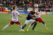 Teal Bunbury #10 of New England Revolution keeps the ball from Dax McCarty #11 and Ambroise Oyongo #3 of New York Red Bulls in the second half during Leg 2 of the MLS Eastern Conference game at Gillette Stadium on November 29, 2014 in Foxboro, Massachusetts.