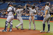 Neil Walker #14 of the New York Yankees is congratulated by Andrew McCutchen #26 and Giancarlo Stanton #27 after hitting all in with a three-run home run as Nick Ciuffo #19 of the Tampa Bay Rays reacts in the first inning of a baseball game at Tropicana Field on September 26, 2018 in St. Petersburg, Florida.