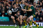 Isaac Luke (L) of New Zealand is tackled by Paul Gallen (R) and Cameron Smith of Australia during the Rugby League World Cup final between New Zealand and Australia at Old Trafford on November 30, 2013 in Manchester, England.