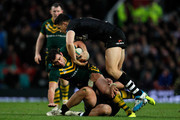 Cameron Smith of Australia is tackled by Sonny Bill Williams (R) and Elijah Taylor of New Zealand during the Rugby League World Cup final between New Zealand and Australia at Old Trafford on November 30, 2013 in Manchester, England.