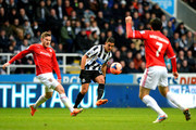 Hatem Ben Arfa of Newcastle crosses under pressure from Aron Gunnarsson (L) of Cardiff during the Budweiser FA Cup third round match between Newcastle United and Cardiff City at St James' Park on January 4, 2014 in Newcastle upon Tyne, England.