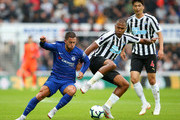 Eden Hazard of Chelsea is challenged by Salomon Rondon of Newcastle United during the Premier League match between Newcastle United and Chelsea FC at St. James Park on August 26, 2018 in Newcastle upon Tyne, United Kingdom.