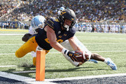 Patrick Laird #28 of the California Golden Bears dives past Jonathan Smith #7 of the North Carolina Tar Heels for a touchdown at California Memorial Stadium on September 1, 2018 in Berkeley, California.