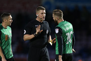 Referee Robert Jones talks to Kevin Van Veen of Scunthorpe United prior to showing him a yellow card  during The Emirates FA Cup First Round match between Northampton Town and Scunthorpe United at Sixfields on November 4, 2017 in Northampton, England.