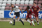 Harry Kane of Tottenham Hotspur moves away with the ball from Paul Rodgers of Northampton Town during a Behind Closed Doors Friendly Match between Northampton Town and Tottenham Hotspur at Sixfields Stadium on October 19, 2010 in Northampton, England.