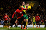 Patrice Evra of Manchester United appears to handle the ball as he is challenged by Ricky van Wolfswinkel of Norwich City during the Barclays Premier League match between Norwich City and  Manchester United at Carrow Road on December 28, 2013 in Norwich, England.