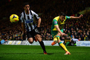 Robert Snodgrass of Norwich City crosses the ball under pressure from Hatem Ben Arfa of Newcastle United during the Barclays Premier League match between Norwich City and Newcastle United at Carrow Road on January 28, 2014 in Norwich, England.