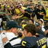 Tate Forcier Photos - Quarterback Tate Forcier #5 embraces head coach Rich Rodriguez as they approach the tunnel after beating Notre Dame 38-34 at Michigan Stadium on September 12, 2009 in Ann Arbor, Michigan. - Notre Dame v Michigan