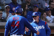 Manager Joe Maddon #70 (R) of the Chicago Cubs high fives Anthony Rizzo #44 after scoring against the Oakland Athletics during the third inning of the spring training game at Sloan Park on February 28, 2018 in Mesa, Arizona.