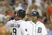 Carlos Guillen #9 of the Detroit Tigers hits a two run home run in the fifth inning and is congratulated by teammate Jhonny Peralta #27 during the game against the Oakland Athletics at Comerica Park on July 19, 2011 in Detroit, Michigan.