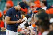 Charlie Morton #50 of the Houston Astros signs autographs during batting practice before playing the Oakland Athletics at Minute Maid Park on August 27, 2018 in Houston, Texas.