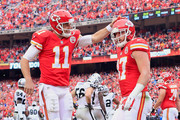 Alex Smith #11 of the Kansas City Chiefs celebrates a touchdown with Travis Kelce #87 during the game against the Oakland Raiders  at Arrowhead Stadium on December 14, 2014 in Kansas City, Missouri.