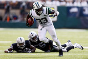 Chris Ivory #33 of the New York Jets rushes after evading tackle attempts by  T.J. Carrie #38 and  Sio Moore #55 of the Oakland Raiders during the third quarter of a game at MetLife Stadium on September 7, 2014 in East Rutherford, New Jersey.