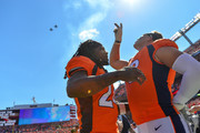 Defensive back Adam Jones #24 and offensive tackle Garett Bolles #72 of the Denver Broncos stand on the field as a pair of jets perform a flyover during the singing of the national anthem before a game against the Oakland Raiders at Broncos Stadium at Mile High on September 16, 2018 in Denver, Colorado.