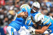 Quarterback Philip Rivers #17 of the Los Angeles Chargers is sacked by defensive end Bruce Irvin #51 of the Oakland Raiders in the first quarter at StubHub Center on October 7, 2018 in Carson, California.