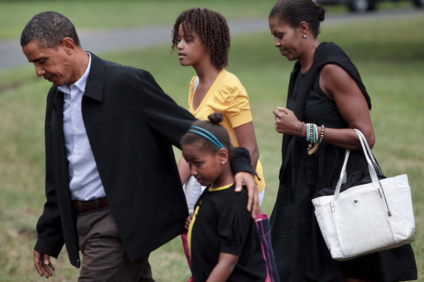 President Barack Obama (L) and First Lady Michelle Obama (R) walk with their daughters Sasha (2L) and Malia (2R) from Marine One on the South Lawn of the White House August 30, 2009 in Washington, DC.  President Barack Obama and the first family returned to Washington after spending a week vacation in Massachusetts's Martha's Vineyard.