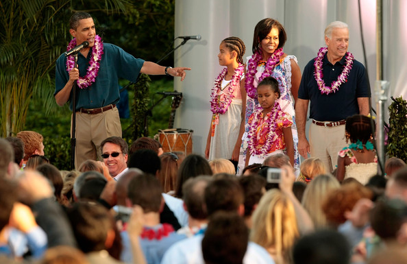 (AFP OUT) Sporting leis, (L-R) U.S. President Barack Obama, Malia Obama, Michelle Obama, Sasha Obama and Vice President Joe Biden host a luau for members of Congress and their families on the South Lawn of the White House June 25, 2009 in Washington, DC. In a celebration of the president's home state, the South Lawn was decorated with tiki torches and palm huts and the meal prepared by famous Hawaiian chef Alan Wong.