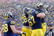 Tight end Devin Funchess #87 of the Michigan Wolverines celebrates a fourth quarter touchdown with teammates against the Ohio State Buckeyes  during a game at Michigan Stadium on November 30, 2013 in Ann Arbor, Michigan.