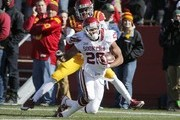 Defensive back Kamari Cotton-Moya #5 of the Iowa State Cyclones tackles running back Alex Ross #28 of the Oklahoma Sooners as he rushed for yards in the first half of play at Jack Trice Stadium on November 1, 2014 in Ames, Iowa.