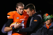 Head coach Mike Gundy of the Oklahoma State Cowboys embraces quarterback J.W. Walsh #4 of the Oklahoma State Cowboys before a game against the Oklahoma Sooners at Boone Pickens Stadium on November 28, 2015 in Stillwater, Oklahoma.