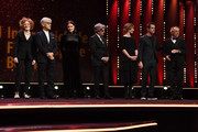 (L-R) Jury members Stephanie Zacharek, Ryuichi Sakamoto, Adele Romanski, Chema Prado, Cecile de France, Jury President Tom Tykwer and Festival director Dieter Kosslick are seem on stage at the Opening Ceremony & 'Isle of Dogs' premiere during the 68th Berlinale International Film Festival Berlin at Berlinale Palace on February 15, 2018 in Berlin, Germany.