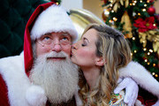 Vanessa Ray turns the tables as she delivers a holiday candle to Santa Claus after unveiling Origins new discovery store concept at at Origins SouthPark on December 4, 2015 in Charlotte, North Carolina.