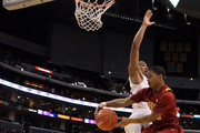 Maurice Jones #10 of the USC Trojans looks to pass the ball to teammate Alex Stepheson #1 around Jesse Perry #33 of the Arizona Wildcats in the second half in the semifinals of the 2011 Pacific Life Pac-10 Men's Basketball Tournament at Staples Center on March 11, 2011 in Los Angeles, California.