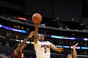 Kevin Parrom #3 of the Arizona Wildcats goes up for a shot between Alex Stepheson #1 and Maurice Jones #10 of the USC Trojans in the first half in the semifinals of the 2011 Pacific Life Pac-10 Men's Basketball Tournament at Staples Center on March 11, 2011 in Los Angeles, California.