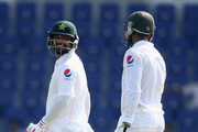 Mohammad Hafeez of Pakistan speaks to Shoaib Malik of Pakistan during Day One of the First Test between Pakistan and England at Zayed Cricket Stadium on October 13, 2015 in Abu Dhabi, United Arab Emirates.