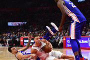 Blake Griffin #32 of the LA Clippers grabs a loose ball in front of Dario Saric #9 and Joel Embiid #21 of the Philadelphia 76ers during the first half at Staples Center on November 13, 2017 in Los Angeles, California.