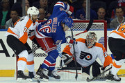 Pierre-Edouard Bellemare #78 and Steve Mason #35 of the Philadelphia Flyers defend against Chris Mueller #86 of the New York Rangers during the first period  at Madison Square Garden on September 29, 2014 in New York City.