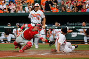 Chris Parmelee #41 of the Baltimore Orioles scores in front of the tag of catcher Carlos Ruiz #51 of the Philadelphia Phillies during the first inning at Oriole Park at Camden Yards on June 16, 2015 in Baltimore, Maryland.