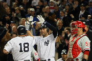 Derek Jeter #2 and Johnny Damon #18 of the New York Yankees celebrate after they scored on a 2-run single by Hideki Matsui #55 as Carlos Ruiz #51 of the Philadelphia Phillies looks on in the bottom of the third inning of Game Six of the 2009 MLB World Series at Yankee Stadium on November 4, 2009 in the Bronx borough of New York City.