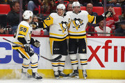 Sidney Crosby #87 of the Pittsburgh Penguins celebrates his first period goal with Justin Schultz #4 and Jake Guentzel #59 while playing the Detroit Red Wings at Little Caesars Arena on March 27, 2018 in Detroit, Michigan.
