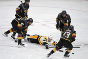 Dominik Simon #49 of the Pittsburgh Penguins dives on the ice as he tries to control the puck against Alex Tuch #89, Pierre-Edouard Bellemare #41, Deryk Engelland #5 and Brendan Leipsic #13 of the Vegas Golden Knights in the third period of their game at T-Mobile Arena on December 14, 2017 in Las Vegas, Nevada. The Golden Knights won 2-1.