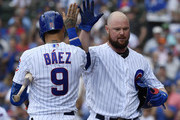 Javier Baez #9 of the Chicago Cubs high-fives Jon Lester #34 of the Chicago Cubs for his solo home run in the third inning against the Pittsburgh Pirates at Wrigley Field on July 13, 2019 in Chicago, Illinois.