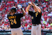 Pedro Alvarez #24 of the Pittsburgh Pirates hits a two-run home run in the third inning and celebrates with Justin Morneau #66 against the St. Louis Cardinals during Game Two of the National League Division Series at Busch Stadium on October 4, 2013 in St Louis, Missouri.