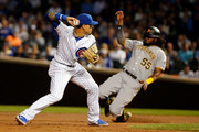 Javier Baez #9 of the Chicago Cubs throws to first base as Josh Bell #55 of the Pittsburgh Pirates slides into second base during the fifth inning at Wrigley Field on September 25, 2018 in Chicago, Illinois.