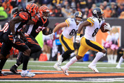 Antonio Brown #84 of the Pittsburgh Steelers runs the ball away from Vontaze Burfict #55 of the Cincinnati Bengals and Dre Kirkpatrick #27 during the fourth quarter at Paul Brown Stadium on October 14, 2018 in Cincinnati, Ohio. Pittsburgh defeated Cincinnati 28-21.