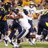 Geno Smith Photos - Geno Smith #12 of the West Virginia Mountaineers evades a tackle from Brandon Lindsey #7 of the University of Pittsburgh Panthers during the 2011 Backyard Brawl on November 25, 2011 at Mountaineer Field in Morgantown, West Virginia. - Pittsburgh v West Virginia