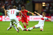 Andrey Arshavin of Russia is tackled by Jakub Blaszczykowski of Poland during the UEFA EURO 2012 group A match between Poland and Russia at The National Stadium on June 12, 2012 in Warsaw, Poland.