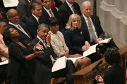 U.S. President Barack Obama wipes away a tear while he and first lady Michelle Obama (C), Dr. Jill Biden (2nd-R) and Vice President Joseph Biden (R), listen to Michele Fowlin (L) direct the Children of the Gospel Choir during the National Prayer Service at the National Cathedral, on January 22, 2013 in Washington, DC. President Obama was sworn in on January 20 for his second term as President of the United States.