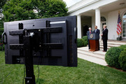 A TV monitor is seen as U.S. President Barack Obama (C) makes a statement to the media as Co-Chairs of BP Oil Spill Commission Bob Graham (L) and William Reilly (R) listen at the Rose Garden of the White House June 1, 2010 in Washington, DC.  Obama had his first meeting with the co-chairs of the commission investigating the deepwater oil spill catastrophe in the Gulf of Mexico prior to his statement.