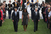 (L-R) U.S. President Barack Obama, first lady Michelle Obama and Vice President Joe Biden walk onto the South Lawn before observing a moment of silence to mark the 13th anniversary of the 9/11 attacks at the White House September 11, 2014 in Washington, DC. Obama and the first lady will travel to the Pentagon later today for another memorial ceremony.