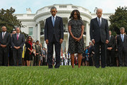 (L-R) U.S. President Barack Obama, first lady Michelle Obama and Vice President Joe Biden observe a moment of silence to mark the 13th anniversary of the 9/11 attacks on the South Lawn of the White House September 11, 2014 in Washington, DC. Obama and the first lady will travel to the Pentagon later today for another memorial ceremony.