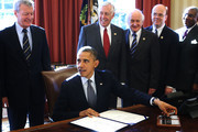 """U.S. President Barack Obama signs H.R. 6156, the Russia and Moldova Jackson-Vanik Repeal and Sergei Magnitsky Rule of Law Accountability Act, into law as (L-R) Sen. Max Baucus (D-MT), House Minority Whip Rep. Steny Hoyer (D-MD), Rep. Sandy Levin (D-MI), Rep. Jim McGovern (D-MA), and Rep. Gregory Meeks (D-NY) look on during an Oval Office event December 14, 2012 at the White House in Washington, DC. According to a White House news release, the bill """"authorizes the President to extend Russia and Moldova with Permanent Normal Trade Relations and will sanction persons who are responsible for gross violations of human rights in Russia."""""""