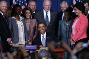 U.S. President Barack Obama (C), joined by (L-R) Vice President Joseph Biden, trafficking survivor Tysheena Rhames, House Minority Leader Rep. Nancy Pelosi (D-CA), Sen. Michael Crapo (R-ID), Sen. Patrick Leahy (D-VT), House Minority Whip Rep. Steny Hoyer (D-MD), Rep. Gwen Moore (D-WI), and Director of Public Policy of Casa de Esperanza Rosemary Hidalgo-McCabe, signs the Violence Against Women Act into law at the Department of the Interior March 7, 2013 in Washington, DC. The law expands protections for victims of domestic violence, sexual assault and trafficking.