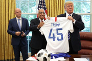 U.S. President Donald Trump (R) holds a U.S. Soccer uniform as he poses for a photograph with U.S. Soccer President Carlos Cordeiro (C) and FIFA President Gianni Infantino in the Oval Office at the White House August 28, 2018 in Washington, DC. The 2026 FIFA World Cup will be jointly hosted by the United States, Canada and Mexico and will be the first World Cup in history to be held in three countries at the same time.